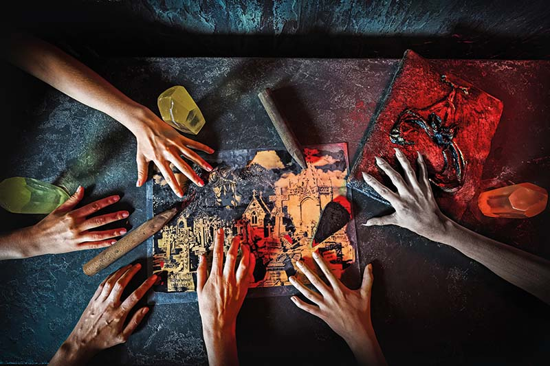 Hænder er samlet på et bord med uhyggelige kort og bøger