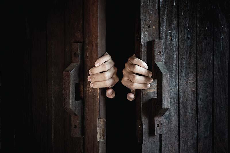 Person åbner en gammel dobbeltdør af mørkt træ ind til et escape room